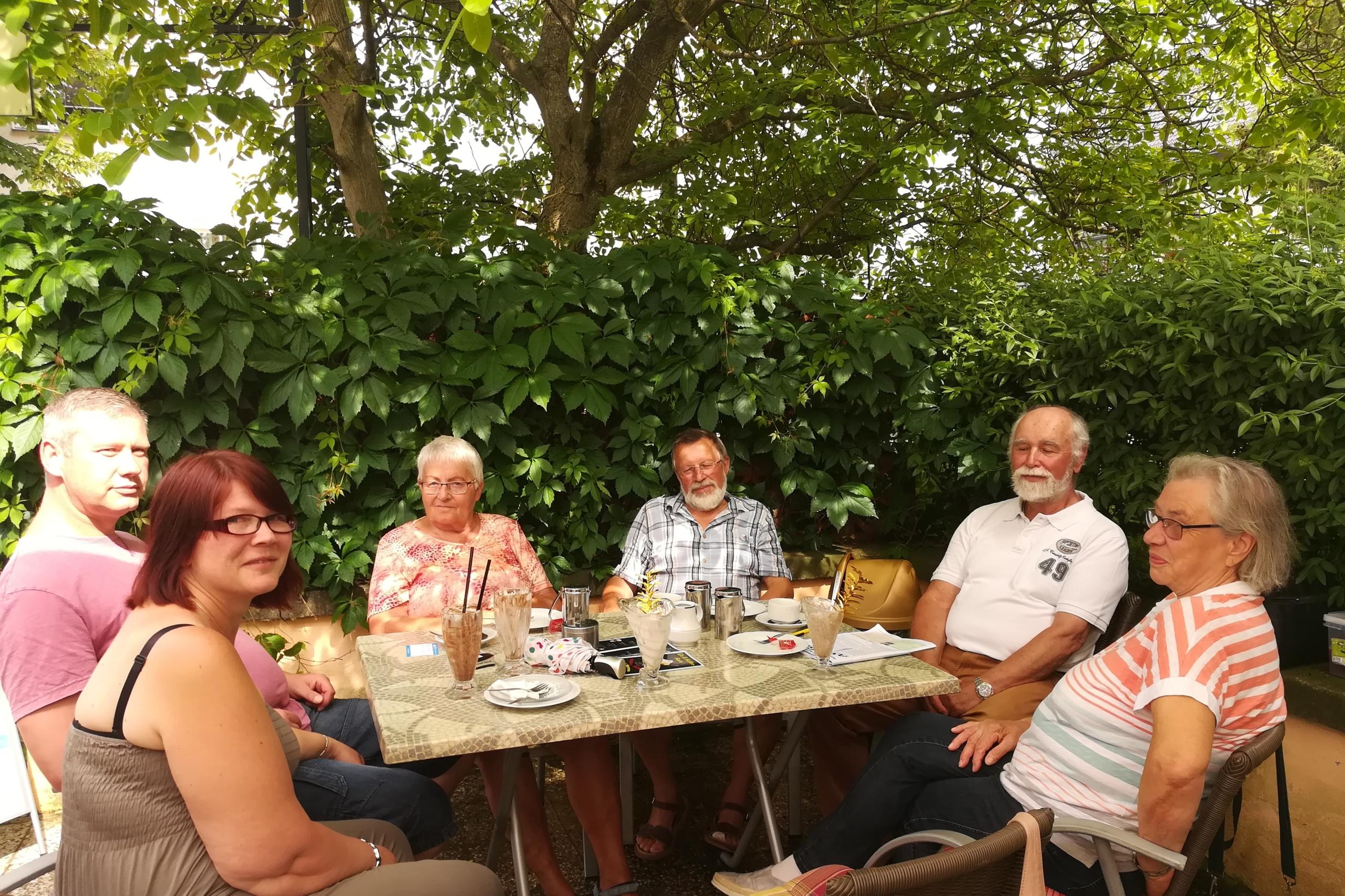 Sechs Personen sitzen um einen Tisch herum